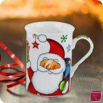 Auf dem Bild sieht man eine Weihnachtstasse die auf einem Tisch steht. Ganz weit hinten im Hintergrund ein verschwommenes Feuer. Neben der Tasse ein wenig abgerolltes rotes schmales Geschenkband. Die Tasse sieht folgendermassen aus, weisse Tasse mit einem Weihnachtsmann bedruckt. Dieser trägt über der Schulter einen Sack, in der anderen Hand nhat er ein paar bunt verpackte Geschenke. An seiner Mütze hängt ein roter Stern. Über dem Weihnachtsmann sieht man eine grüne Schneeflocke und einen blauen Stern. Der Henkel der Tasse mist weihnachtlich bedruckt.