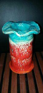 Auf diesem Bild sieht man eine selbstgestaltete Vase in den Farben rot und blau. Der Rand der Vase ist in einem wellenförmigen Format . Diese Vase wurde selbst getöpfert und auch verziert mit unterschiedlichen Intarsien. Zum Schluss wurde die Vase noch mit Klarlack überzogen so dass sie glänzt. Die Vase ist innen und außen bemalt.