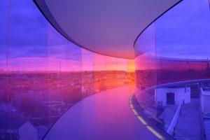Auf diesem Bild sieht man in verschiedenen Episoden eine Brücke, es handelt sich dabei um eine gläserne Brücke die geschwungen ist. Sie ist in Kurvenform. Auf beiden Seiten der Brücke sieht man Häuser , Wolken , Sonnenstrahlen und ein Farbenspiel von blau lila rosa und Orange Farbtönen.