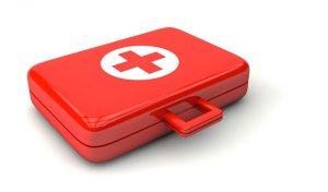 Auf diesem Bild ist ein verschlossener roter Koffer zu sehen. Auf dem Koffer ist ein weisser durchgehender Kreis, wo nur in der Mitte ein rotes Kreuz zu sehen ist, auch der Handgriff des Koffers ist in rot. Der Hintergrund ist in weiss.