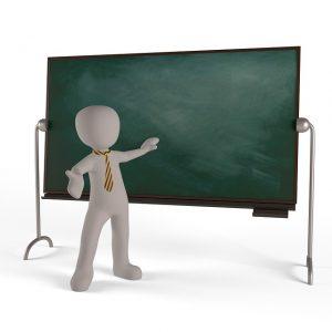Auf diesem Bild sieht man eine große grüne Tafel, besser bekannt unter Kreidetafeln aus der Schule. Davor steht eine Karikatur, die einen Lehrer darstellen soll. Die Karikatur ist bekleidet mit einer gelb gemusterten Krawatte.