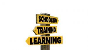 Dieses Bild zeigt einen Wegweiser, der gelbe Weg Schilder hat. Die Schilder zeigen in unterschiedliche Richtungen und sind beschriftet. Auf den Schildern steht von oben nach unten gesehen , Schulung , Training und Lernen.