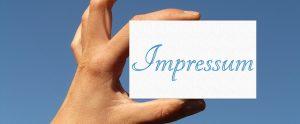 Auf dem Bild ist eine weisse Karte mit dem hellblauen Aufdruck Impressum zu sehen. Die Karte wird von einer Hand zwischen Daumen und Zeigefinger im Querformat gehalten. Der Hintergrund ist in blau.
