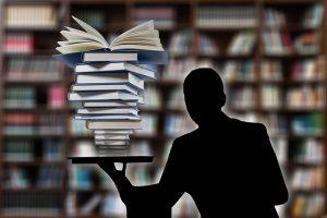 Auf diesem Bild sieht man im Hintergrund ganz verschwommen die Regale einer Bibliothek. Im Vordergrund sieht man den Oberkörper einer Person, die mehrere gestapelte Bücher in der Hand trägt. Die Person ist in der Farbe schwarz dargestellt, der Bücherstapel in weiss mit schwarzen Umrahmung der einzelnen Bücher.