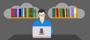Auf diesem Bild sieht man einen Mann an einem Laptop sitzend arbeiten . Sein Laptop steht auf einem grauen Tisch. Der Mann ist bekleidet mit einem blauen Oberhemd und trägt eine Brille. Hinter ihm sind zwei Bücherregale mit mehreren Handbüchern sowohl als auch etwas dickeren Büchern. Die Regale sind umrahmt in hellgrauen Wolken , der Hintergrund ist in dunkelgrau.
