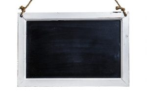 Auf diesem Bild sieht man einen weißen Rahmen aus Holz , in der Mitte befindet sich eine schwarze Tafel Punkt diese Tafel gleicht einer alten Schiefertafel.