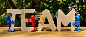Auf diesem Bild sieht man vier große Buchstaben, die das Wort Team bilden. Die Buchstaben sind dargestellt als Einzelbuchstaben in Großschrift und aus hellem Holz oder aus Pappe. Vor den Buchstaben sind vier kleine Figuren zu sehen , in unterschiedlichen Farben , hellblau , dunkelblau, rot und gelb. Die Buchstaben und die Figuren stehen auf einem Tisch oder Holzplatte . Der Hintergrund sieht aus wie Sträucher.