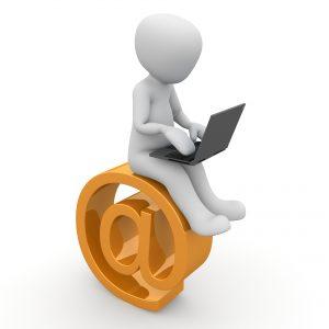 Auf diesem Bild sieht man das @ Symbol in orange Farben abgebildet. Auf dem Symbol sitzt eine kleine Figur die einen aufgeklappten Laptop auf den Oberschenkeln liegen hat. Die Figur versucht an dem Laptop zu arbeiten. Der Hintergrund der Darstellung ist in weiß.