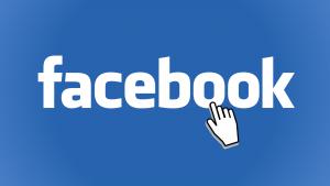 Auf diesem Bild sieht man den weißen Schriftzug von Facebook gedruckt auf einen blauen Hintergrund , in dem zweiten o von Facebook, ist eine kleine weiße Hand als Cursor Symbol dargestellt.