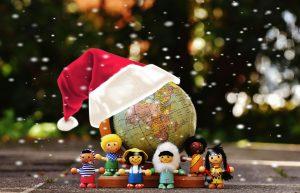 Auf diesem Bild ist eine weihnachtlich dekorierte Weltkugel zu sehen, die eine rote Zipfelmütze trägt mit einem weißen Saum. Vor der Weltkugel stehen kleine Playmobil Figuren, aus unterschiedlichen Nationen bzw Ländern. Im Hintergrund sieht man verschwommen Bäume und Häuser. Im Vordergrund wirkt es wie leichter Schneefall.