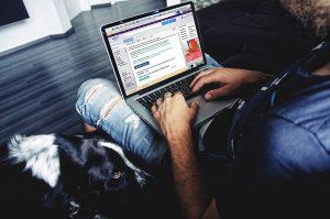 Auf diesem Bild sieht man einen Mann sitzen, der einen aufgeklappten Laptop auf seinen Beinen hat , links neben ihm sitzt ein schwarz-weißer Hund. Der Mann ist im Internet am surfen bzw auf der Suche nach bestimmten Internetadressen. Im Hintergrund sieht man einen schwarzen Fussboden, weiße Wände, und an der hinteren Wand ist ein Fernseher befestigt. Von dem Mann sieht man , dass er eine Jeans trägt und ein blaues Shirt.