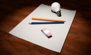 Auf diesem Bild sieht man ein Blatt Papier liegend auf einer Tischplatte. Auf diesem Blatt Papier liegen zwei Bleistifte, einer in blau oder in orange, darunter liegt ein Radiergummi und oberhalb der beiden Stifte liegt eine weiße Glühlampe. Das Blatt Papier liegt zentriert in der Mitte des Bildes, wodurch man die Maserung des Tisches erkennen kann . Die beiden Bleistifte sind angeordnet wie der Buchstabe v.