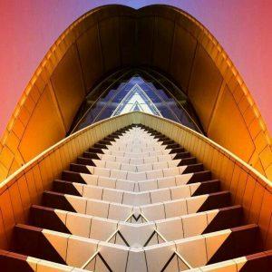 Auf dem Bild sieht man eine langgezogene Treppe die nach oben hin spitz zu läuft. Ähnlich wie die Eingangstreppen bei italienischen Kirchen. Der Hintergrund ist pastellrot. Die Treppe sowie der Eingangsbereich sind in einem gelborange Farbton.Die Treppe wird eingefasst von zwei Handläufen, unterhalb dieser sind rechts und links jeweils ein Teilstück der Treppe in dunkeler Farbe, der Rest der Stufen ist in hellbeige. Der Teil des Eingangsbereichs ist bis auf ein mittiges Dreieck in dunkelblau mit grau, fast wie Glasmalerei. Das Dreieck in der Mitte ist in blau und pastellblau.