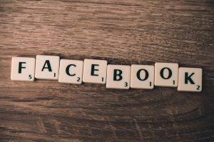 Auf diesem Bild sieht man acht Buchstaben eines Scrabble Spiels aneinandergereiht auf einem Holztisch liegen. Die Buchstaben ergeben das Wort Facebook . Jeder einzelne Buchstabe ist ein kleines Kästchen was den Buchstaben und eine kleine Ziffer enthält.