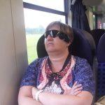 Auf diesem Bild sieht man eine Frau, die in einem Zug sitzt. Sie sieht wie folgt aus, mittel- bis dunkelblonde Haare, sie trägt eine Brille an deren Seite die kleine Kamera des Argus 2 befestigt ist. Bekleidet ist sie mit einem bunt bedruckten T-Shirt. An ihrer rechten Hand trägt sie einen silbernen Ring, links ein weisses Armband.
