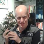 Auf diesem Bild sieht man einen jungen Mann, der in seiner rechten Hand ein iPhone hält. Im Hintergrund sieht man einen geschmückten Weihnachtsbaum und eine Anrichte mit Büchern. Er trägt einen schwarz-grauen Langarmpullover, seine Haare sind hellblond und er lächelt.