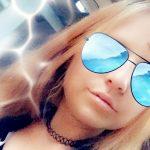 Auf dem Bild ist eine Frau zu sehen, sie trägt ihre langen Haare offen. Bekleidet ist sie mit einem dunklen Oberteil und einer Sonnenbrille, die verspiegelt ist. Die Gläser schimmern in hellblau, die Reflektion sieht wie ein Bild eines langen Weges aus. Der Hintergrund ist in blau und ab und zu schimmert eine Art Blitz durch.