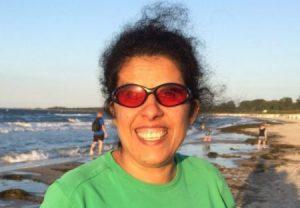 Auf diesem Bild sieht man eine Frau die lacht. Sie hat dunkle gelockte Haare, die nach hinten zusammen gebunden sind. Zusätzlich trägt sie eine rot-orange getönte Sonnenbrille. Bekleidet ist sie mit einem grünen T-Shirt. Im Hintergrund sieht man das Meer und eine kleine Gruppe von Menschen, die im Meer bzw am Strand sich bewegen.
