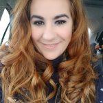 Auf dem Bild sieht man eine Frau, die in einem Auto sitzt. Sie trägt ihre leicht gelockten Haare offen, sie lacht in die Kamera. Ihre Augen werden auf dem Bild durch das dezente Make up betont. Bekleidet ist sie mit einem dunkelblauen Oberteil.