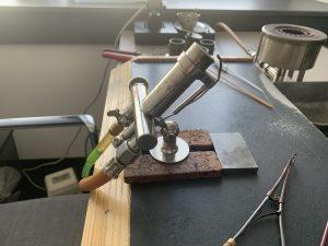 Auf einem Tisch ist ein Bunsenbrenner montiert. Dabei handelt es sich um ein Metallrohr, das etwa 45 Grad nach oben geneigt ist. Am oberen Ende kommt bei Benutzung eine Flamme heraus, auf dem Bild ist der Brenner jedoch aus. Unten an dem Rohr befindet sich ein kleines Querrohr mit zwei Gasanschlüssen.